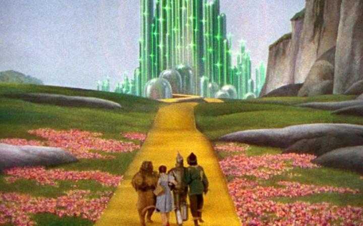 Image du film Le Magicien d'Oz de Victor Fleming (1939) où le lion, Dorothé, l'homme de fer et l'épouvantail (qu'on voit de dos) avance vers un palais magique et lumineux vert sur un chemin jaune entouré de prairies avec des fleurs et des falaises sur la droite.