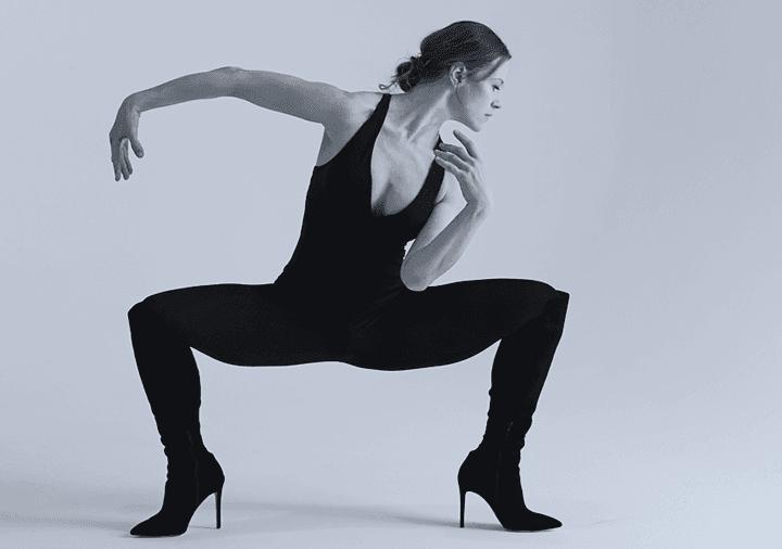 Photo de Lora Juodkaite en justocorps et collants noirs, chaussures noires à talons, elle tient assise sur ses pieds, les jambes écartées sur les côtés (genoux en angles droits) avec son bras gauche replié vers elle et son bras droit tendue