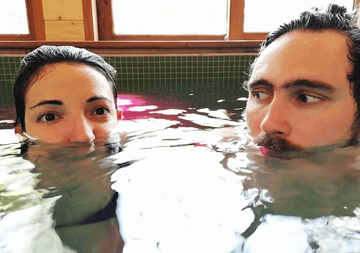 Photo de Paola Stella Minni et Konstantinos Rizos plongés dans un bain, leurs têtes sortent de l'eau jusqu'au nez
